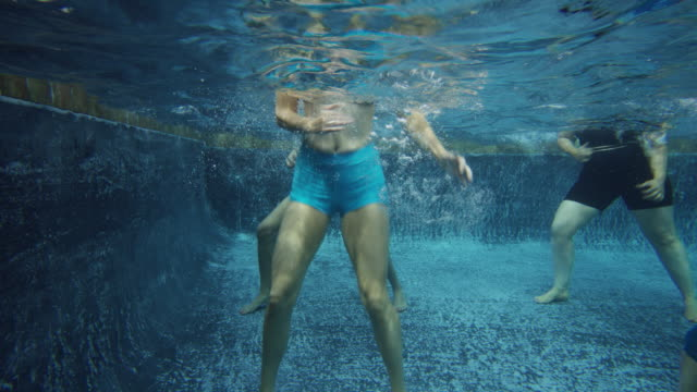 underwater view of men and women in aerobic dancing class in swimming pool / cedar hills, utah, united states - nederdel bildbanksvideor och videomaterial från bakom kulisserna
