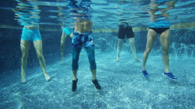 underwater view of men and women in aerobic dancing class in swimming pool / cedar hills, utah, united states - rebellion stock videos & royalty-free footage