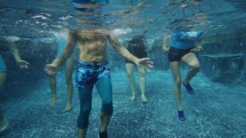 underwater view of men and women in aerobic dancing class in swimming pool / cedar hills, utah, united states - 踏む点の映像素材/bロール