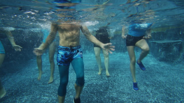 vídeos de stock e filmes b-roll de underwater view of men and women in aerobic dancing class in swimming pool / cedar hills, utah, united states - passos