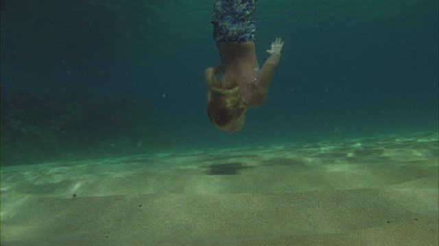 SLO MO, WS, Underwater view of mother and son (6-7) swimming in ocean, Oahu's North Shore, Hawaii, USA