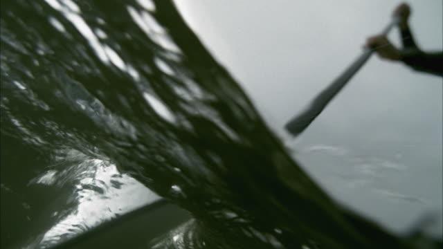 slo mo cu la underwater view of paddle boarder gliding on surface / aspen, colorado, usa - remo video stock e b–roll