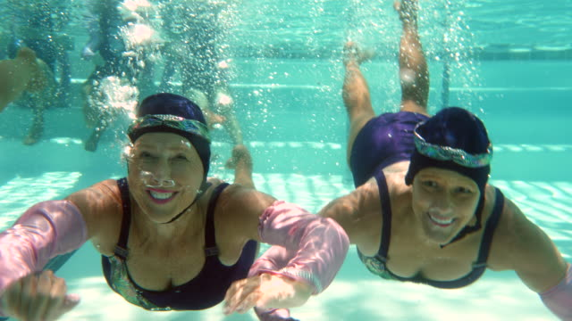 vídeos de stock e filmes b-roll de ms underwater view of smiling senior female synchronized swimmers practicing routine in pool - mulheres maduras