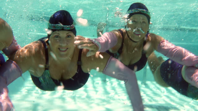 ms underwater view of smiling senior female synchronized swimmers - four people stock videos & royalty-free footage