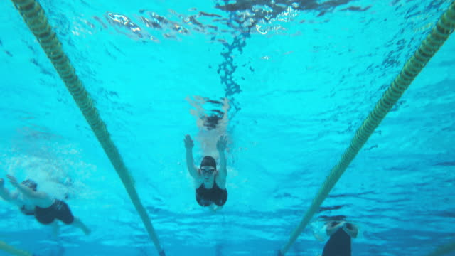Underwater view of swimmers at female breaststroke style competition