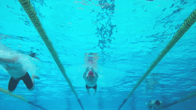 Underwater view of swimmers at male breaststroke style competition