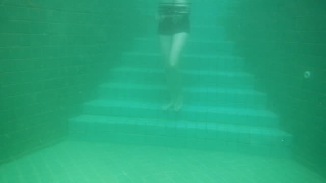 underwater view of woman diving into swimming pool - swimming shorts stock videos & royalty-free footage