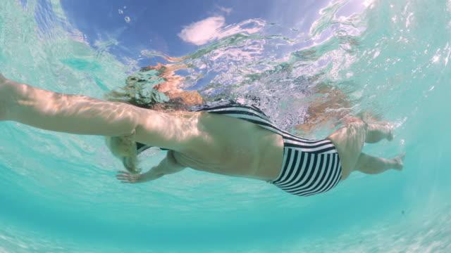 stockvideo's en b-roll-footage met underwater view of woman floating on back in ocean in tahiti / bora bora, french polynesia - menselijke rug