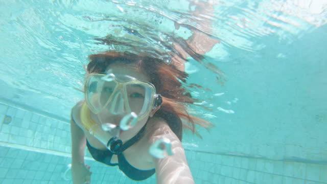 スイミングプールの夏休みで楽しんで水中の女性リラクゼーションシュノーケリングセルフ - インフィニティプール点の映像素材/bロール