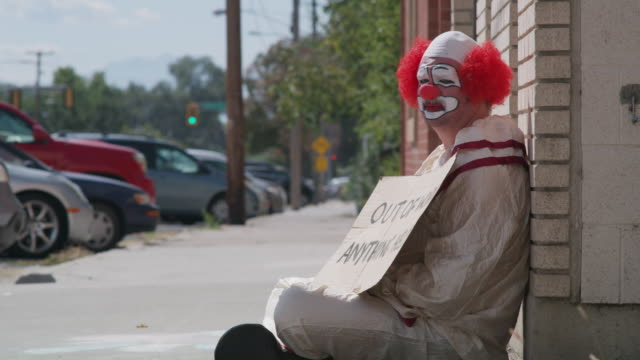 Unemployed clown sitting on sidewalk holding cardboard sign / American Fork, Utah, United States