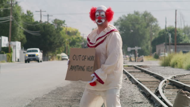 unemployed clown standing in traffic holding cardboard sign / american fork, utah, united states - unemployment stock videos and b-roll footage