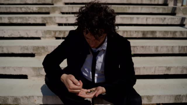 失業中の絶望的なストレス若い男性は、コロナウイルスの間にコインを数え、控えました。 - 減少点の映像素材/bロール