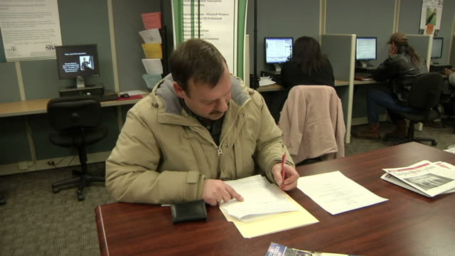 vídeos de stock e filmes b-roll de ms unemployed worker filling out paperwork and applications at michigan works job center, jackson, michigan, usa - formulário documento