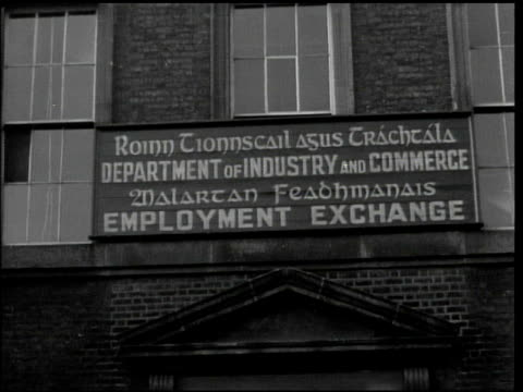 vídeos de stock e filmes b-roll de unemployment exchange building bilingual sign on building ws peat being distributed to people in line men shoveling from stored reserve weighing men... - 1944