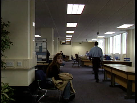 unemployment figures; job centre int cms jobs on board in job centre l-r cms man being intvwd at desk in cms ditto - job centre stock videos & royalty-free footage
