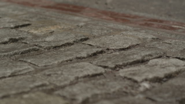 uneven raised bricks in a  brick road. - uneven stock videos & royalty-free footage