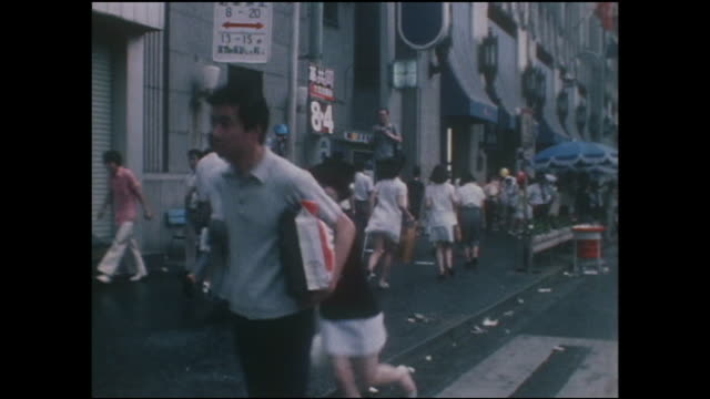 unexpected rain sends pedestrians running across ginza street during pedestrian paradise. - showa period stock videos & royalty-free footage
