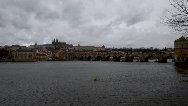 ungraded pan across a stormy cloudy castle and charles bridge in prague czech republic - 聖ヴィート大聖堂点の映像素材/bロール