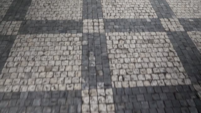 stockvideo's en b-roll-footage met ungraded close up walking across the street stones of prague - grijs
