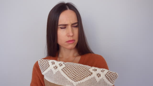 unhappy and sad woman embracing a lace pillow isolated over white background - cushion stock videos and b-roll footage