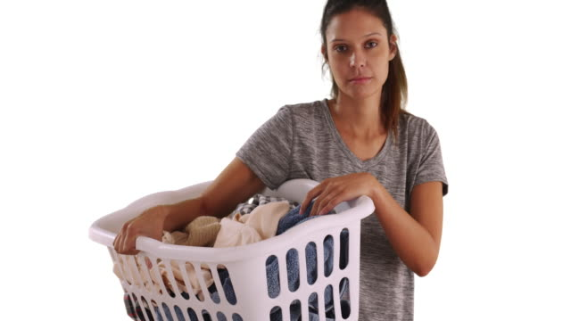 unhappy attractive girl holding basket of dirty clothes on white background - laundry detergent stock videos and b-roll footage