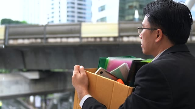 stockvideo's en b-roll-footage met ongelukkig zakenman permanent en verzorgen buiten met zijn bezittingen in een doos papier worden afgevuurd. - ontslaan