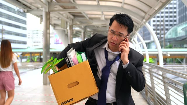 unhappy businessman talking with mobile phone and carrying his belongings in a paper box after being fired. - unemployment stock videos and b-roll footage