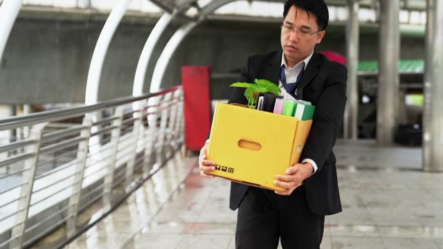 unhappy businessman walking and carrying his belongings in a paper box after being fired. - carrying stock videos & royalty-free footage
