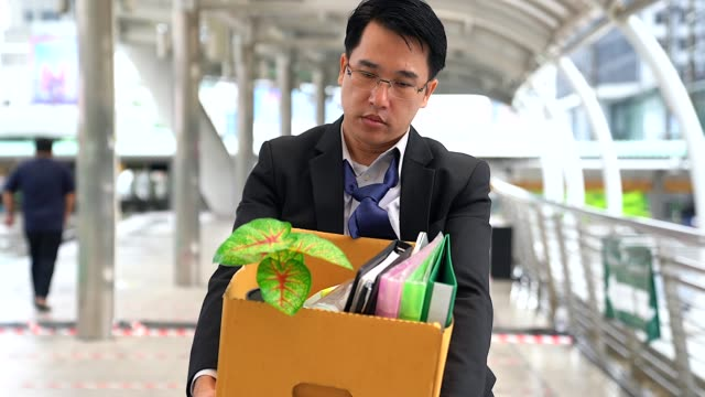 unhappy businessman walking and carrying his belongings in a paper box after being fired. - fallimento video stock e b–roll