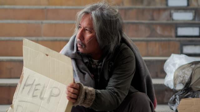 vidéos et rushes de malheureux homme sans-abri tient à aident des mains pour obtenir la main de l'homme de help.homeless. bénévolat, ce qui donne - besoin