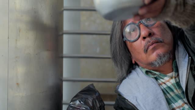 vídeos de stock, filmes e b-roll de infeliz homem sem-teto está segurando as mãos para pegar a mão do homem help.homeless ajudam. voluntariado, dando - falência