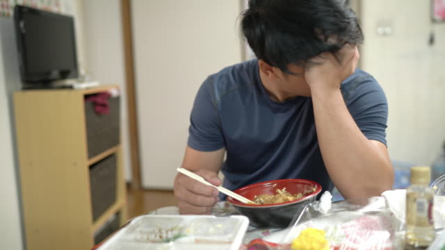 不幸な孤独な悲しい男は、自宅のダイニングルームに座って昼食を食べて - 孤独点の映像素材/bロール