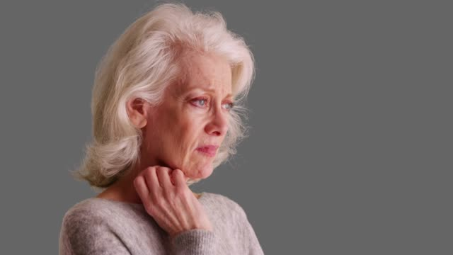 unhappy older woman with sad pensive expression sighing on grey background - gray background stock videos & royalty-free footage