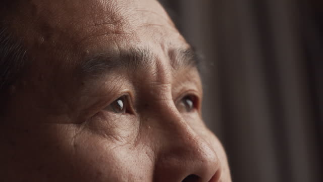 unhappy senior asian man sitting on a sofa and feeling worry and depress about his money financial at home - senior men stock videos & royalty-free footage