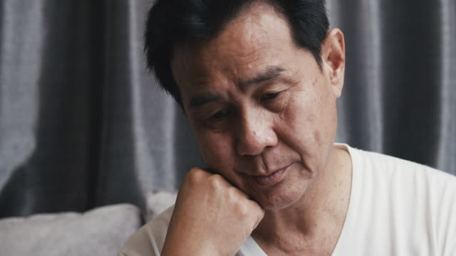 unhappy senior asian man sitting on a sofa and feeling worry and depress about medical result from hospital at home - sad old asian man stock videos & royalty-free footage