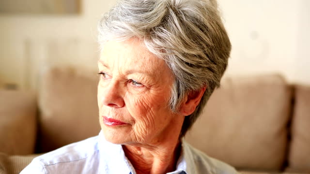 Unhappy senior woman sitting on couch