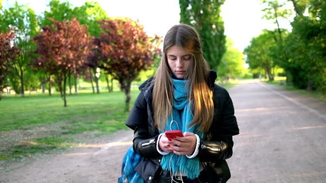 Unhappy teenage girl in the city park text messaging