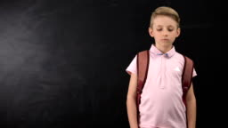 Unhappy tired schoolboy standing near chalkboard, suffering overload at school