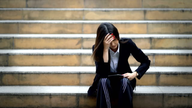 4k unhappy young businesswoman was frustrated and sitting on staircase at modern city background, stress woman has headache and touching head, sadness and depression concept - frustration asian failure stock videos & royalty-free footage