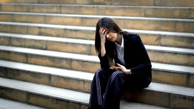 4k unhappy young businesswoman was frustrated and sitting on staircase at modern city background, stress woman has headache and touching head - frustration asian failure stock videos & royalty-free footage