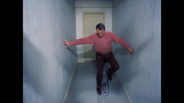 stockvideo's en b-roll-footage met unicyclist practicing in hallway - oefenen