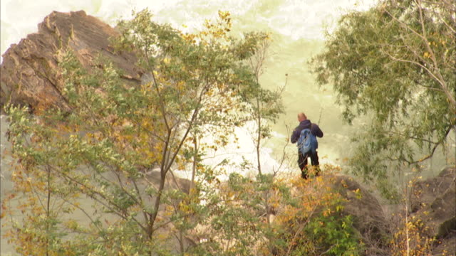 Unidentifiable adult male wearing backpack standing on rock at edge of Niagara River Whirlpool fishing w/ pole trees FG river BG ZO XWS Niagara River...