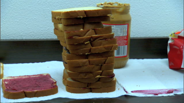 MS Unidentifiable African American female's hand placing peanut butter bread on top of jelly jam bread adding sandwich to stack of PBJ sandwiches on...