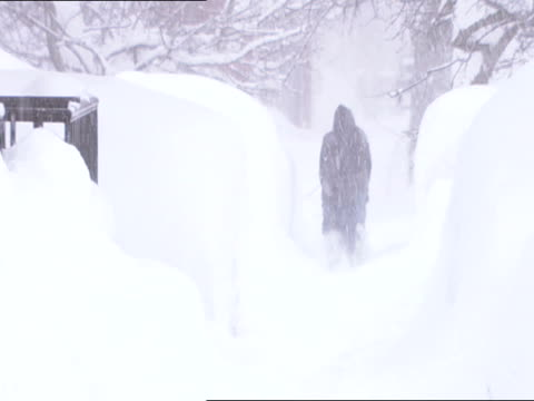 unidentifiable female form in jacket mittens walking down snow covered sidewalk piles of snow edged w/ drifts heavy snowing td legs boot walking... - mitten stock videos and b-roll footage