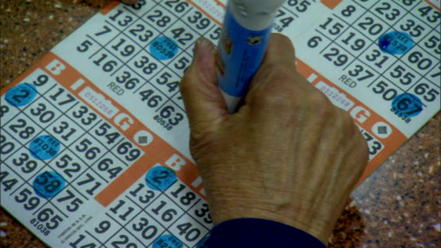 vídeos y material grabado en eventos de stock de unidentifiable female hand using blue dauber marker to mark numbers on bingo card as they are called game gamble gambler gambling lottery recreation - bingo