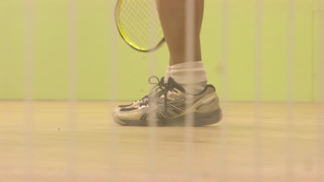 unidentifiable female lower body legs socks shoes standing on squash court holding racket down second female joining bg hitting ball female waiting... - squash sport stock videos & royalty-free footage