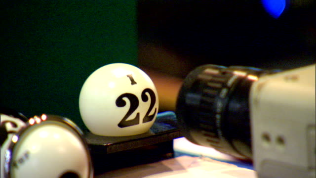 stockvideo's en b-roll-footage met ecu unidentifiable female placing white numbered plastic balls in front of camera lens calling out numbers bingo lottery air ping pong balls random... - bingo