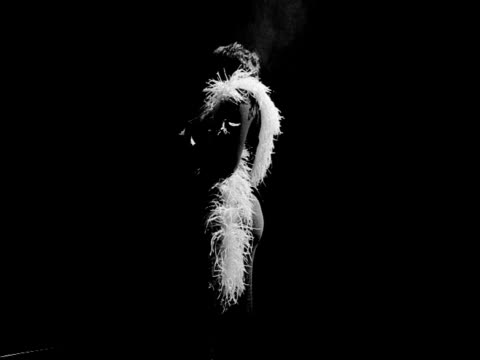unidentifiable female standing on smokey stage wearing feather boa around neck, frontal features in deep shadow, high back lighting. comedian, master... - b rolle stock-videos und b-roll-filmmaterial