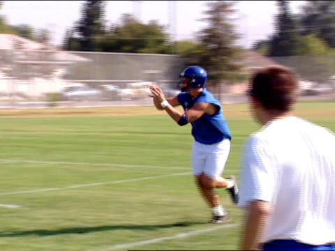 unidentifiable football player catching pass during drill on football field. - practice drill stock videos & royalty-free footage