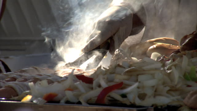 unidentifiable hand w/ food clamp, cooking hot dogs wrapped in bacon, onions & peppers cooking on the side. carnival, fair, festival, street stand,... - schraubstock stock-videos und b-roll-filmmaterial